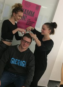 Jugendesekretär wird von zwei Friseurinnen Haare geschnitten.