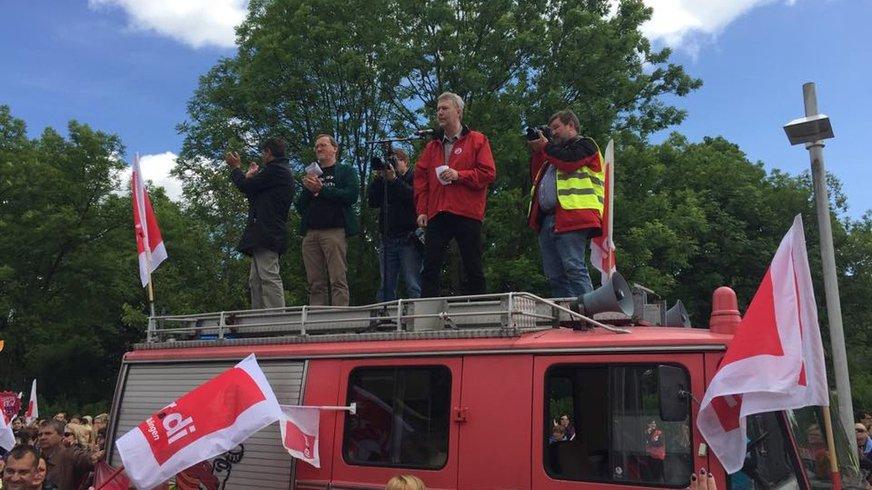 Bild eines ver.di Feuerwehrwagens auf dem Menschen stehen