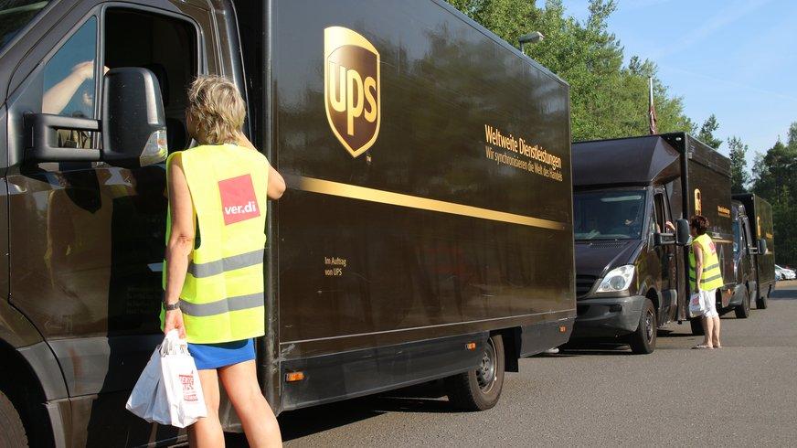 ver.di-Mitarbeiterin in gelber Warnweste verteilt Infos an UPS-Fahrer