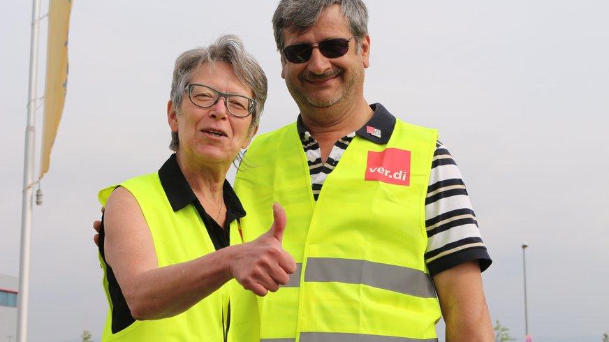 Eine Frau und ein Mann in verdi Weste schauen lachend in die Kamera. Die Frau hält den Daumen hoch.