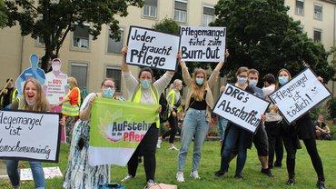 """Junge Pflegekräfte halten Schilder hoch: """"Pflegemangel führt zum Burnout"""", """"Pflegemangel ist menschenunwürdig"""""""